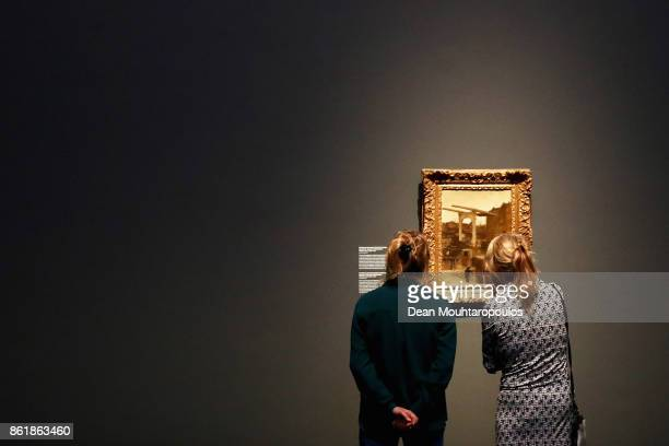 Visitors look at The Nieuwe Haarlemse Sluis on the Singel Known as Souvenir d'Amsterdam by Matthijs Maris during a special exhibition held at the...