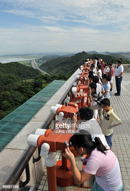 Visitors look at the North Korean side from a South Korean observation tower near the Demilitarized zone in Paju north of Seoul on August 21 2009...