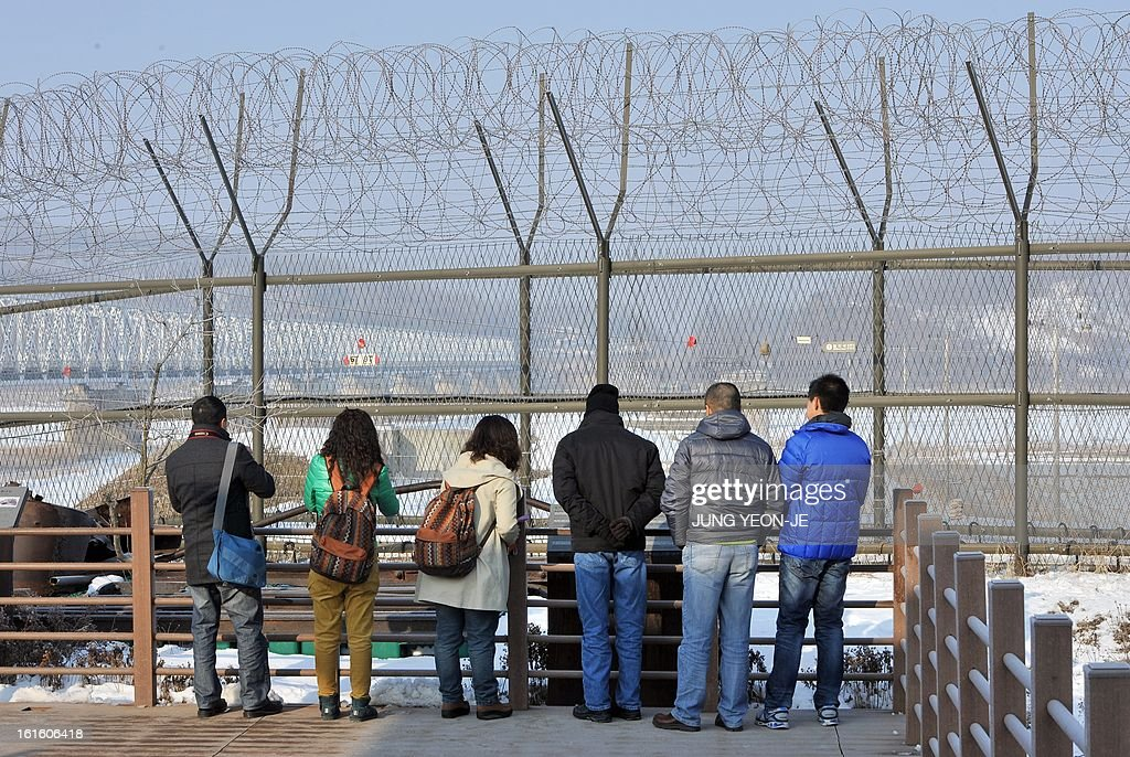Visitors look at the North side over a military iron fence at Imjingak peace park in Paju near the demilitarized zone dividing the two Koreas on February 13, 2013. South Korea said on February 13 it would accelerate the development of longer-range ballistic missiles that could cover the whole of North Korea in response to a third nuclear test by Pyongyang.