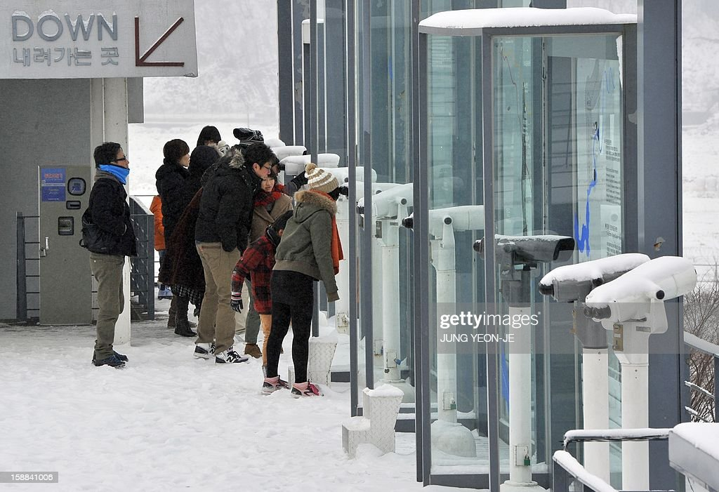 Visitors look at the North side through binoculars at an observation tower of Imjingak peace park in Paju near the Demilitarized Zone (DMZ) dividing the two Koreas on January 1, 2013. North Korean leader Kim Jong-Un called on January 1, 2013 for an easing of tensions with the South and flagged a 'radical turnabout' in the national economy in a rare voiced message broadcast on state television.