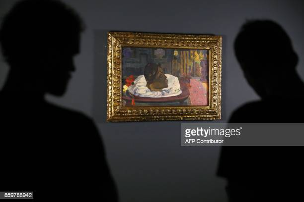 Visitors look at the painting 'Arii Matamoe ' by French painter Paul Gauguin during the exhibition entitled 'Gauguin the alchimist' at the Grand...