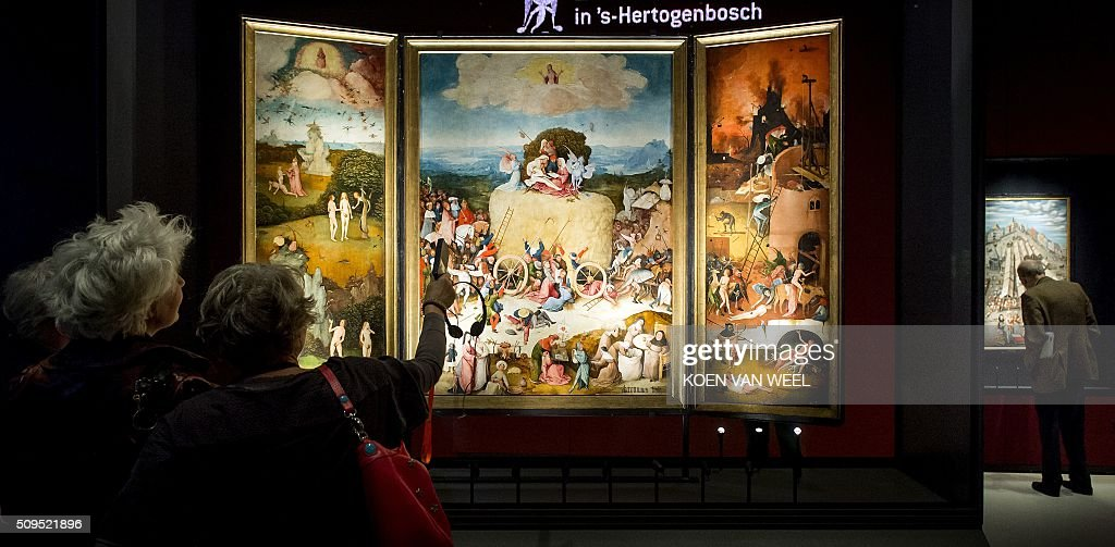 Visitors look at the painting 'De Hooiwagen' (The Haywain Triptych) painted by Dutch Renaissance artist Jheronimus Bosch (or Hieronymus, or Jeroen Bosch) during a press preview of the exhibition 'Hieronymus Bosch - Visions of a Genius' at the Noordbrabants Museum in Den Bosch on February 11, 2016. The exhibition will run from February 13 till May 8, 2016. / AFP / ANP / Koen van Weel