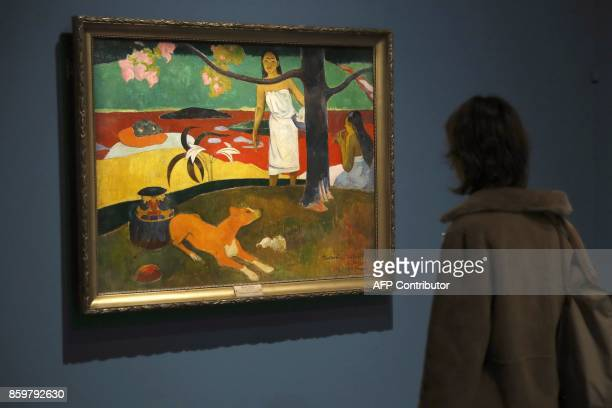 Visitors look at the painting 'Faa Iheihe ' by French painter Paul Gauguin during the exhibition entitled 'Gauguin the alchimist' at the Grand Palais...