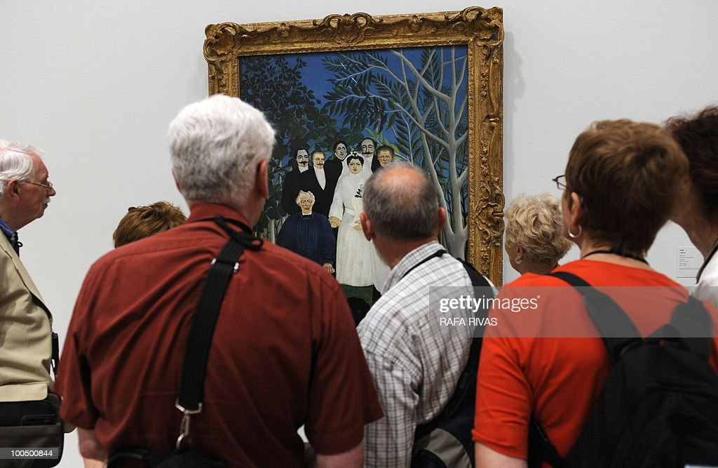 Visitors look at the painting 'La Noce' by French painter Henri Rousseau during the temporary exhibition 'Henri Rousseau' at the Guggenheim Bilbao museum on May 25, 2010, in the Northern Spanish Basque city of Bilbao. The exhibition, opened from May 25 untill September 12, 2010, includes thirty masterpieces providing a review of the French painter's career.