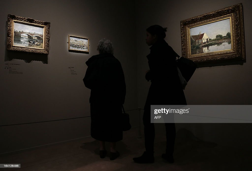 Visitors look at the paintings ,'le pont de Deauville' (L), 'laveuses' (C), and 'coin de ferme ', on March 20, 2013 at the Jacquemart-Andre museum during the inaugural visit to the French painter Eugene Boudin's (1824 - 1898) exhibition running from March 22 to July 22, 2013.