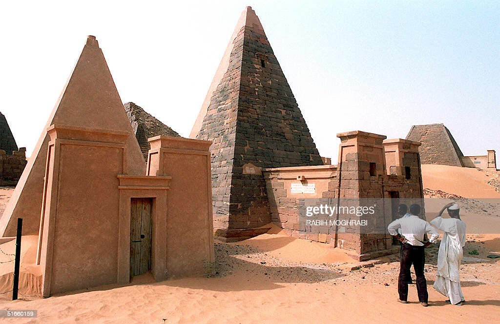 Visitors look at the pyramids of the Sudanese kingdom of Meroe 08 March in Sudan. Some 40 pyramids, which were the homes of 20 Meroeite kings, eight queens, three royal princes and a dozen of nobles whose rule spanned nearly five centuries from 592 B.C. to 350 A.D., rise from the desert, 70 kms north of the town of Shendi.