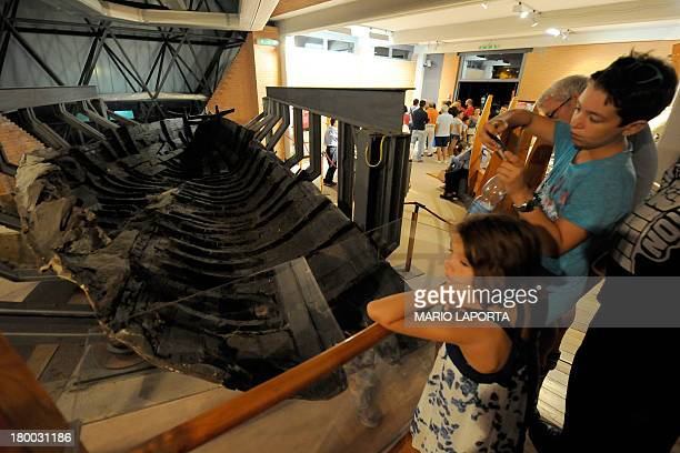 Visitors look at the remains of a boat from ancient Herculaneum at an exhibition in the Hercolaneum Ruins Museum in Ercolano the city destroyed by...