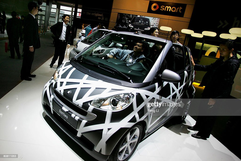 A visitors look at the Smart Fortwo during a special media opening of the Auto China 2008 show at the new China International Exhibition Center on April 21, 2008 in Beijing, China. The annual auto show is held from April 20-28 with 890 vehicles including 55 concept cars on show.