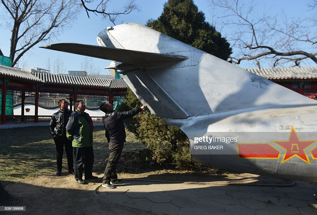 Visitors look at the tail of an old Chinese fighter jet in a park in Beijing during Lunar New Year celebrations on February 9, 2016. Millions of Chinese are celebrating Spring Festival, the most important holiday on the Chinese calendar, which this year marks the beginning of the Year of the Monkey. AFP PHOTO / GREG BAKER / AFP / GREG BAKER