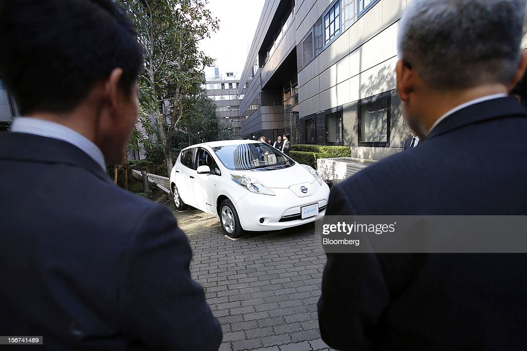 Visitors look at the updated Nissan Leaf electric vehicle (EV) produced by Nissan Motor Co. during a news conference in Japan, Tokyo, on Tuesday, Nov. 20, 2012. Nissan Motor Co., Japan's second-largest carmaker, introduced a cheaper version of the Leaf electric vehicle to lure cost-conscious buyers as sales of the original model lag behind the company's target. Photographer: Kiyoshi Ota/Bloomberg via Getty Images