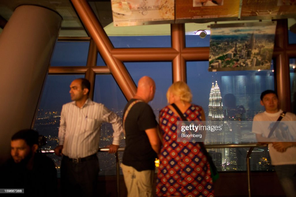 Visitors look at the view from the observation deck at Kuala Lumpur Tower as the Petronas Towers stand illuminated at night in Kuala Lumpur, Malaysia, on Wednesday, Jan. 16, 2013. While many developed countries have faltered, Malaysia's gross domestic product growth has exceeded 5 percent for five quarters with domestic demand countering a slowdown in exports. Photographer: Lam Yik Fei/Bloomberg via Getty Images