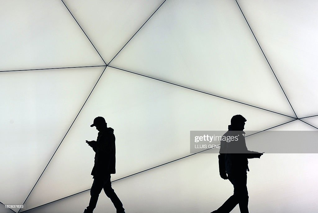 Visitors look at their mobile phones during the last day at the 2013 Mobile World Congress in Barcelona on February 28, 2013. The 2013 Mobile World Congress, the world's biggest mobile fair, is held from February 25 to 28 in Barcelona.