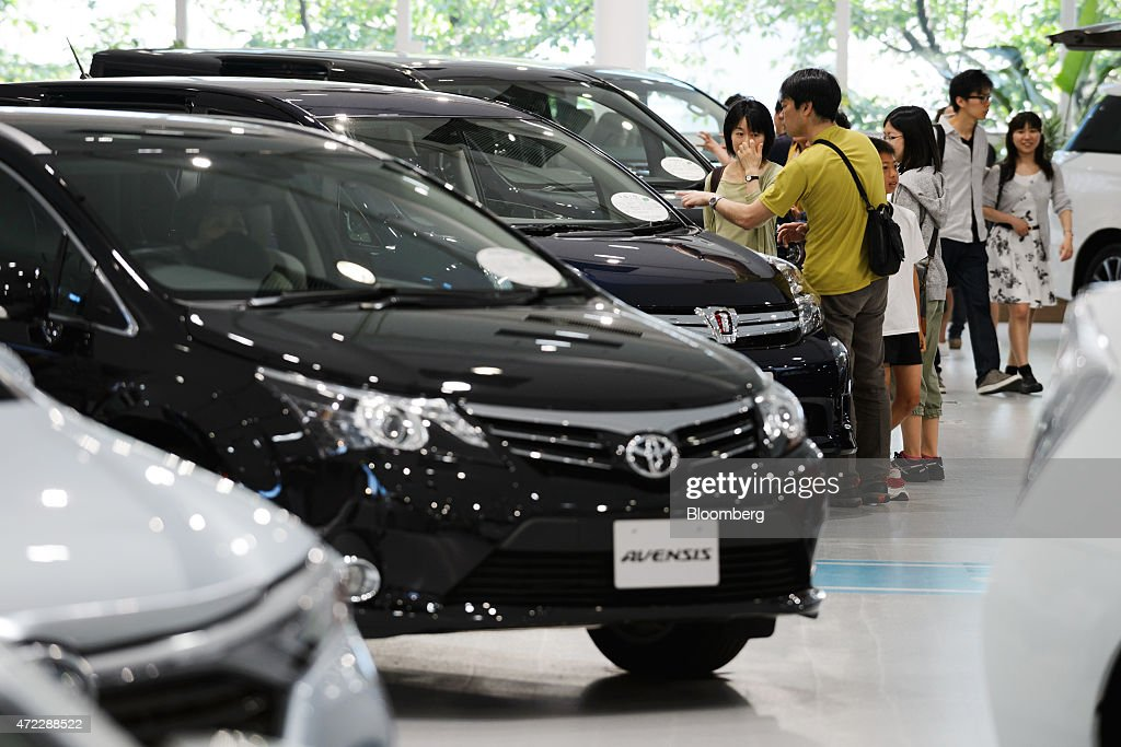 Visitors look at Toyota Motor Corp vehicles on display at the company's Mega Web showroom in Tokyo Japan on Tuesday May 5 2015 Toyota Motor Corp the...