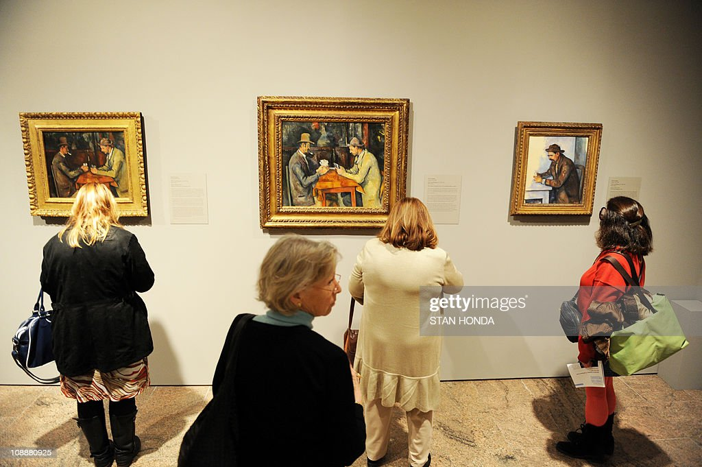 Visitors look at versions of 'The Card Players' (L and C) 1892-96 and 'The Card Player' (R) 1892-96 by Paul Cézanne on February 7, 2011 at the Metropolitan Museum of Art in New York during a preview for the exhibition, 'Cezanne's Card Players.' The show unites works from the famous series by Cézanne, bringing together a majority of the related paintings, oil studies, and drawings. The three paintings are on loan from the Musee d'Orsay in Paris (L) and The Samuel Courtauld Trust, The Courtauld Gallery, London (C) and the Musee d'Orsay (R). AFP PHOTO/Stan HONDA
