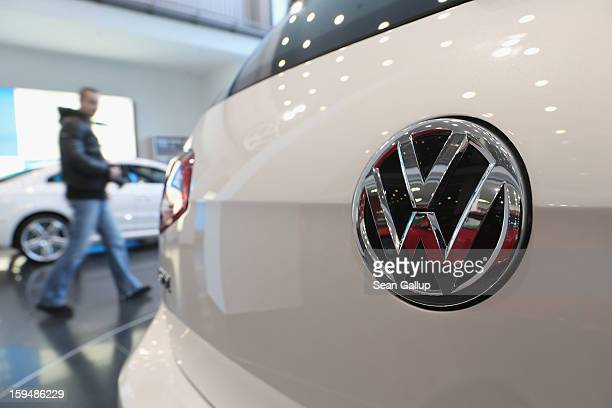 Visitors look at VW cars at a Volkswagen Group showroom on January 14 2013 in Berlin Germany Volkswagen Group which includes the VW Audi Porsche...