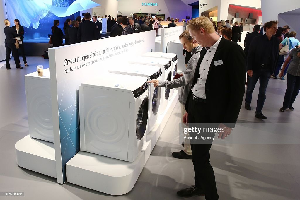 Visitors look at washing machine at the Siemens stand at the 2015 IFA consumer electronics and appliances trade fair on September 4 2015 in Berlin...