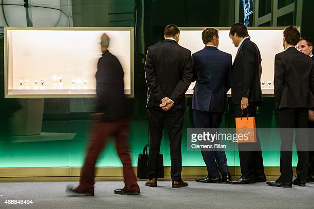 Visitors look at watches that are on display at the Rolex booth during Baselworld 2015 on March 19 2015 in Basel Switzerland
