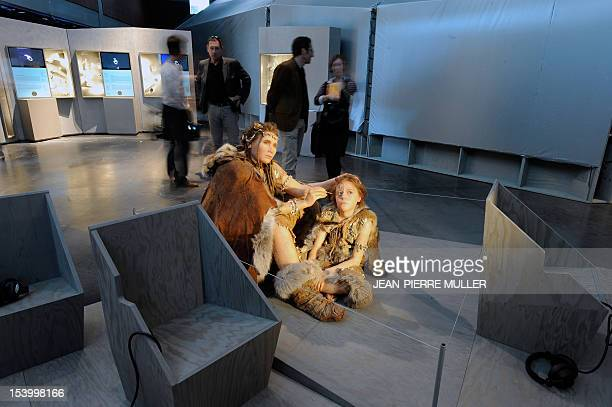 Visitors look at wax figures representing the CroMagnon humans the early Homo sapiens sapiens such as those who painted in the Lascaux caves...