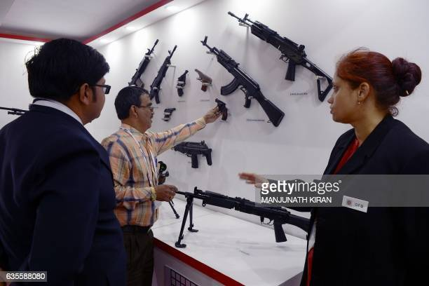 Visitors look at weapons on display at a stall in the exhibition area on the third day of the 11th edition of 'Aero India' a biennial international...