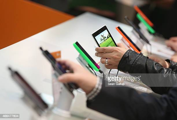 Visitors look at Windowsenabled smartphones including the Nokia Lumia series at the Microsoft stand the 2015 CeBIT technology trade fair on March 16...