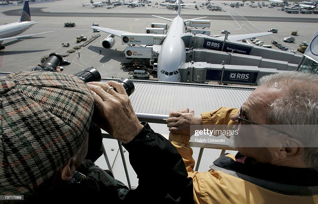 Visitors look down from a viewing platform near a parked Airbus A380 at Frankfurt Airport on March 27, 2007 in Frankfurt, Germany. The 555-seat double-decker A380 returned from a test flight of Lufthansa and Airbus Industries from Washington to test airport function and compatibility of the world's largest passenger aircraft.