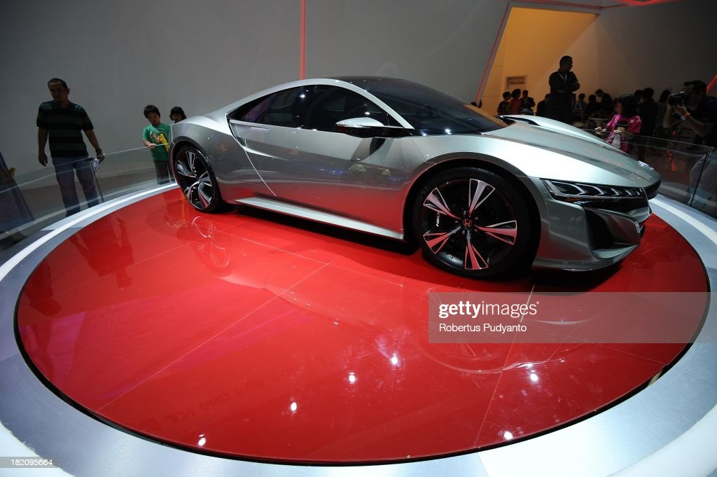 Visitors look into Honda NSX on display at Honda booth during The 21st Indonesia International Motor Show 2013 on September 28 2013 in Jakarta...