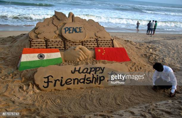 Visitors look near to a sand sculpture creating by sand artist Sudarshan Pattnaik to spread message about ChinaIndia friendship on the International...