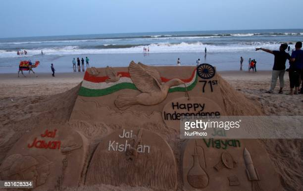 Visitors look near to the Independence Day sand sculpture creating by sand artist Sudarshan Patnaik at the Bay of Bengal Sea's eastern coast beach at...