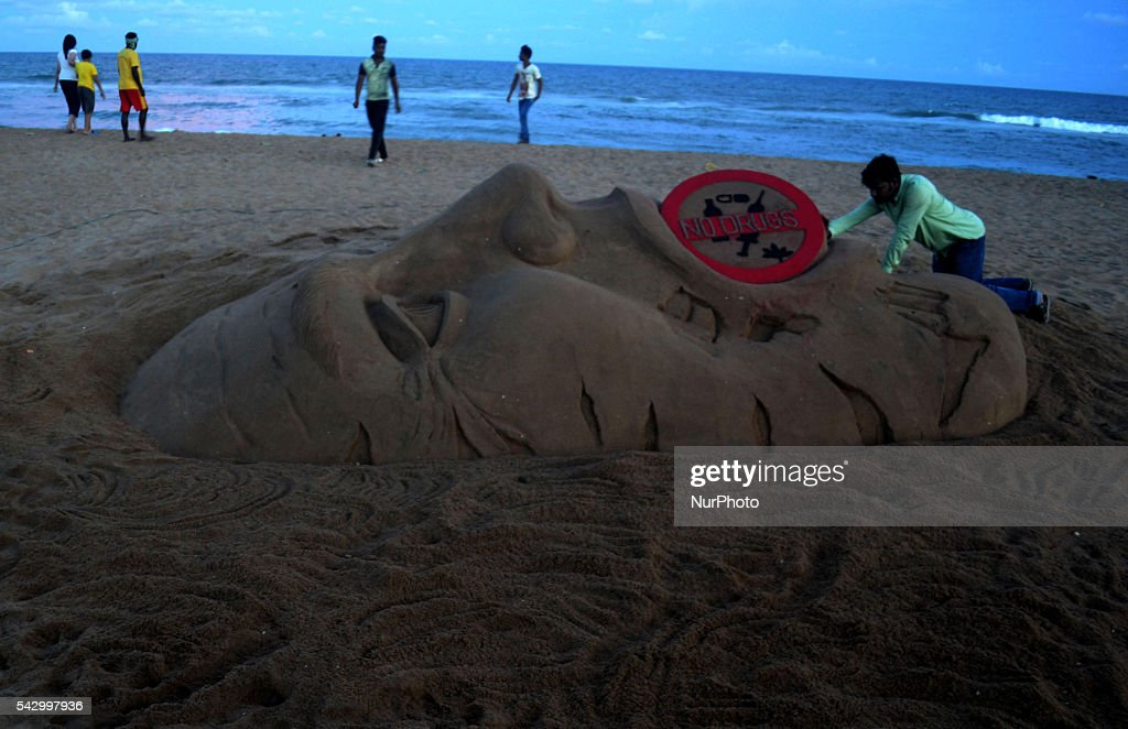 Visitors look near to the Rio Olympic sand sculpture, creating by sand artist Sudarshan Pattnaik after Indian runner Dutee Chand qualify for upcoming Olympic games at the Bay of Bengal Seas eastern coast beach at Puri, 65 km away from the eastern Indian city Bhubaneswar, India, Saturday, 25 June 2016.