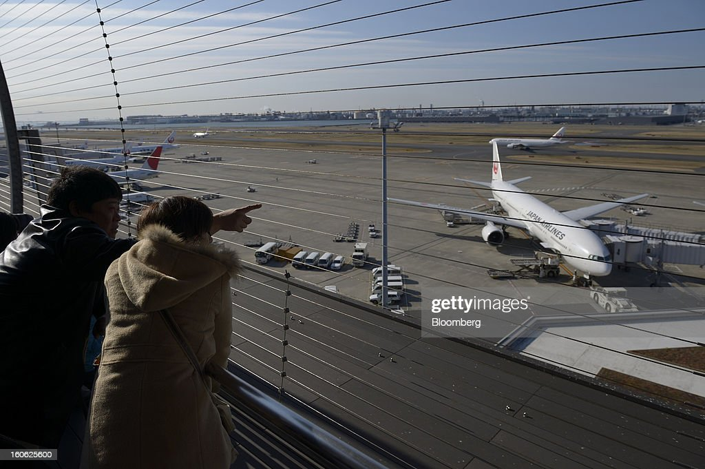 Visitors look on and point from an observation deck as Japan Airlines Co. (JAL) aircraft stand parked on the tarmac at Haneda Airport in Tokyo, Japan, on Sunday, Feb. 3, 2013. Japan Airlines, the nation's largest carrier by market value, is scheduled to release earnings on Feb. 4. Photographer: Akio Kon/Bloomberg via Getty Images