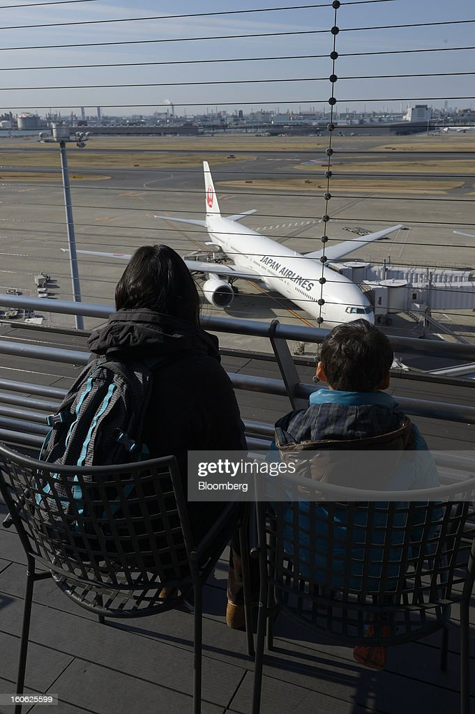 Visitors look on from an observation deck as Japan Airlines Co. (JAL) aircraft stand parked on the tarmac at Haneda Airport in Tokyo, Japan, on Sunday, Feb. 3, 2013. Japan Airlines, the nation's largest carrier by market value, is scheduled to release earnings on Feb. 4. Photographer: Akio Kon/Bloomberg via Getty Images