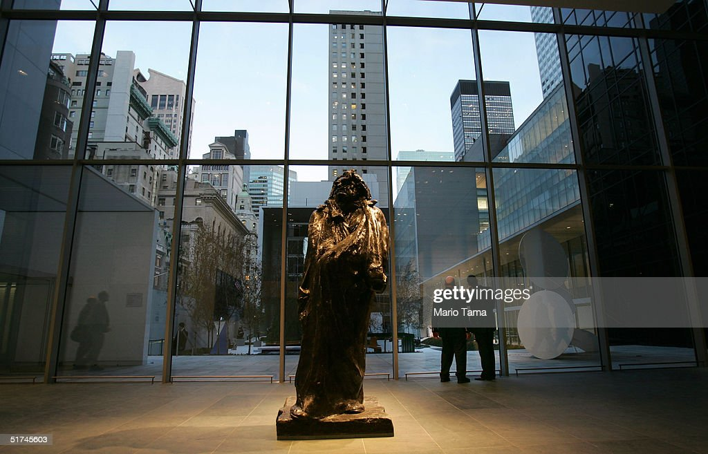 Visitors look out a window at the Sculpture Garden in the newly remodeled Museum of Modern Art during a media preview November 15 2004 in New York...