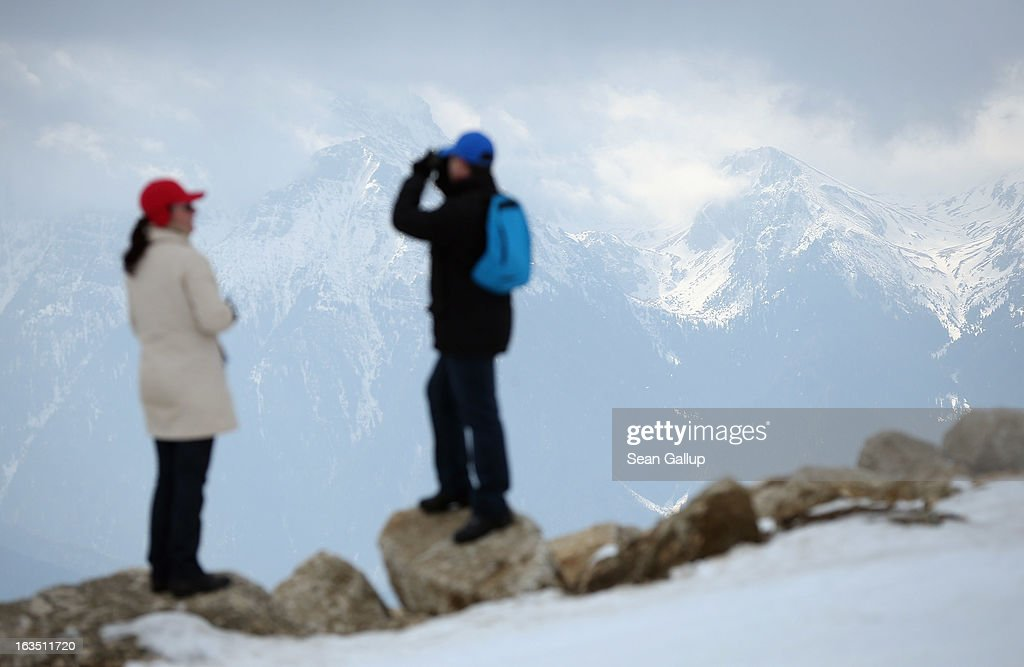 Visitors look out at the Bucegi mountains from the Poiana Brasov ski resort on March 9, 2013 at Poiana Brasov, Romania. Romania is eager to promote its approximately 20 ski resorts, of which Poiana Brasov is among the biggest, to foreign tourists. Both Romania and Bulgaria have been members of the European Union since 2007 and restrictions on their citizens' right to work within the EU are scheduled to end by the end of this year. However Germany's interior minister announced recently that he would veto the two countries' entry into the Schengen Agreement, which would not affect labour rights but would prevent passport-free travel.