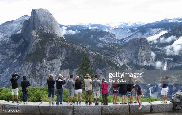 Visitors look out at Yosemite National Park from Glacier Point on July 21 2014 in Yosemite National Park California Yosemite is among California's...