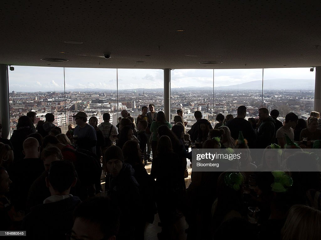 Visitors look out over the Dublin city skyline from the viewing gallery in the Guinness Gravity Bar at the company's St. James's Gate Brewery, in Dublin, Ireland, on Saturday, March 16, 2013. Ireland's renewed competiveness makes it a beacon for the U.S. companies such as EBay, Google Inc. and Facebook Inc., which have expanded their operations in the country over the past two years. Photographer: Simon Dawson/Bloomberg via Getty Images