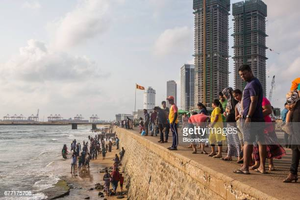 Visitors look out to sea at Galle Face Green as the under construction ShangriLa Hotel Colombo stands in the background in Colombo Sri Lanka on...