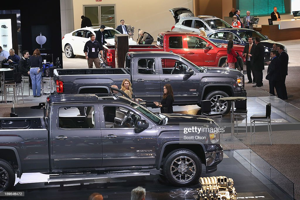 Visitors look over a GMC trucks during the media preview at the North American International Auto Show on January 15, 2013 in Detroit, Michigan. The auto show will be open to the public January 19-27.
