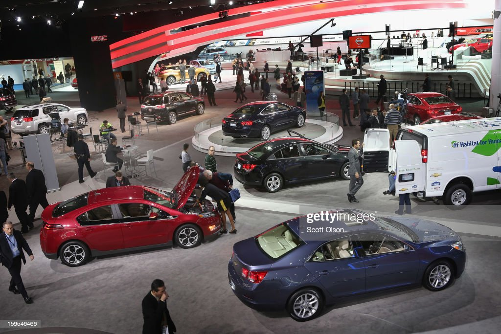 Visitors look over vehicles during the media preview at the North American International Auto Show on January 15, 2013 in Detroit, Michigan. The auto show will be open to the public January 19-27.