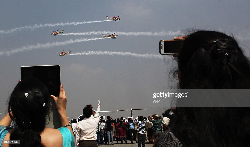 Visitors look the Indian Air Force Sarang aerobatics team perform during the second day of the ongoing 9th Edition of Aero India Show 2013 in Bangalore on February 7, 2013. India, the world's leading importer of weaponry, is hosting one of Asia's biggest aviation trade shows with Western suppliers eyeing lucrative deals and a Chinese delegation attending for the first time. AFP PHOTO/ STR