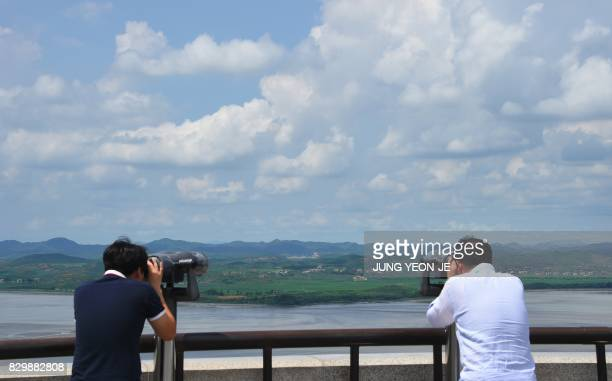 Visitors look through binoculars towards North Korea from a South Korean observation post in Paju near the Demilitarized Zone dividing two Koreas on...