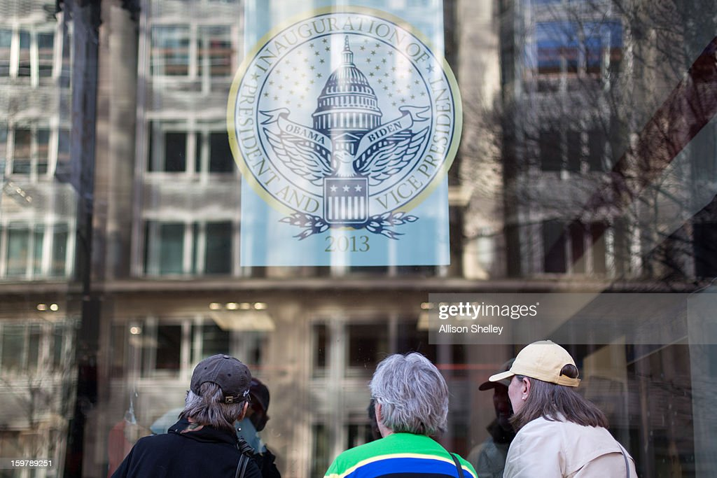 Visitors look through the window of the official inauguration merchandise store January 20, 2013 in Washington D.C. Despite this crowd, souvenir vendors are reporting slow sales compared to the 2009 inauguration, which brought crowds of unprecedented size to the capital.