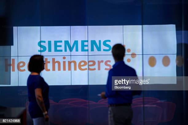 Visitors look towards a display screen inside the Siemens AG Healthineers showroom in Forchheim Germany on Wednesday July 19 2017 Siemens said it's...