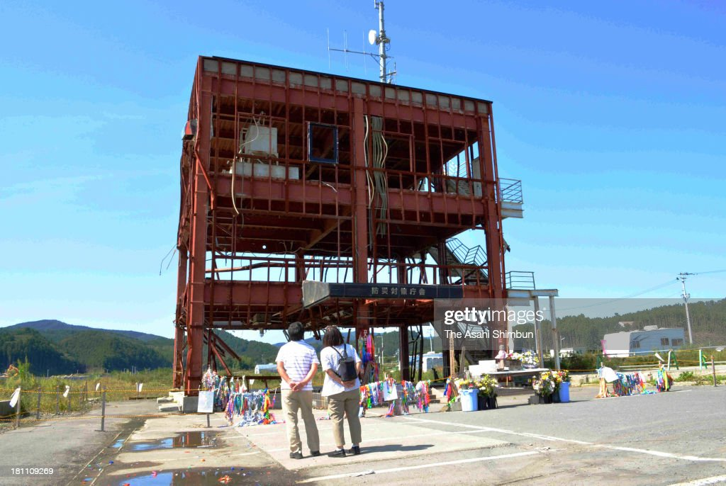Visitors look up the former Minamisanriku disaster prevention center building on September 19, 2013 in Minamisanriku, Miyagi, Japan. The town originally planned to preserve the rusted skeleton of the disaster prevention center building, but the structure has proven to be a painful reminder to many of the 15,000 residents, and the community has now agreed it is scheduled to be demolished.