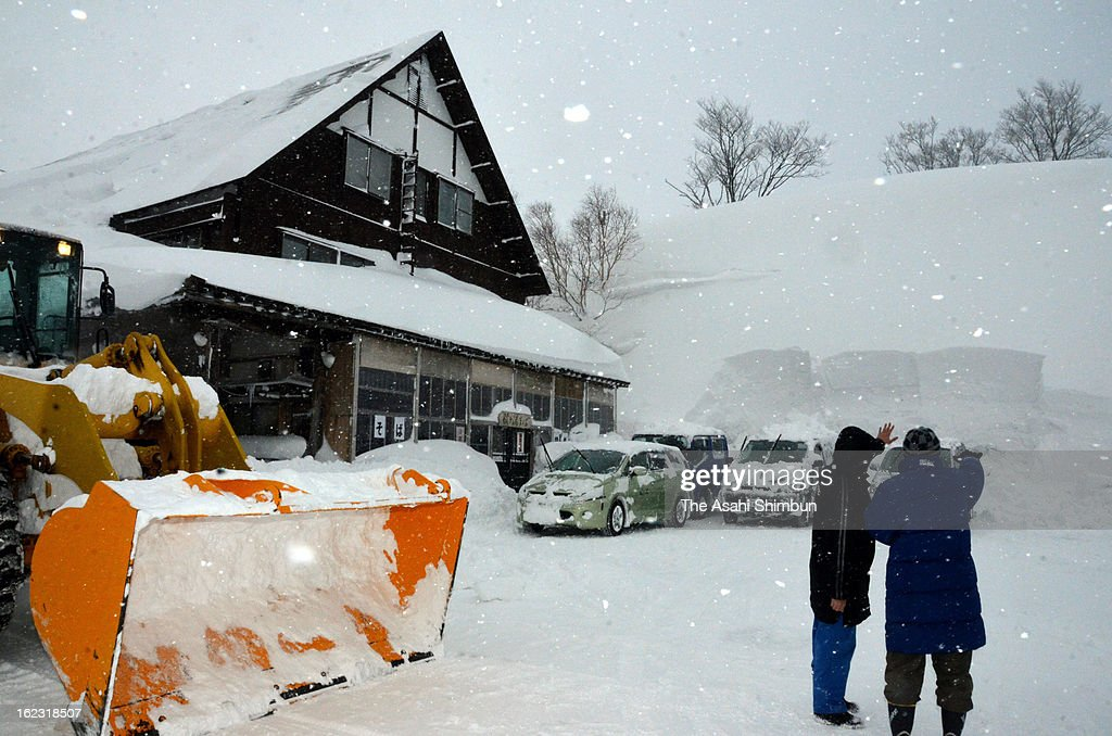 Visitors look up the snow wall at Sukayu hot spring area on February 21, 2013 in Aomori, Japan. 515 centimeters of snow fall is observed at 1 p.m, breaks the former record of 502 centimeters in 1979.