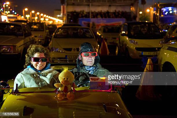 Visitors look with special 3D glasses from their car to the latest Disney movie Planes during the drivein movie theater on the parking of Amsterdam...