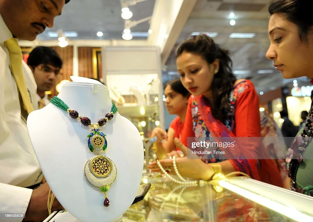 Visitors looking for Jewellery at an exhibitors stall during the Indian Gem and Jewellery Fair on April 12, 2013 in New Delhi, India. Over 100 jewellers and designers are participating in the IGJF held from 12th - 15th April, 2013. One of the largest market of gold, India imported $39.5 billion of gold in first nine months of last fiscal and exported gold jewellery to the tune of $12.12 billion in the same period.