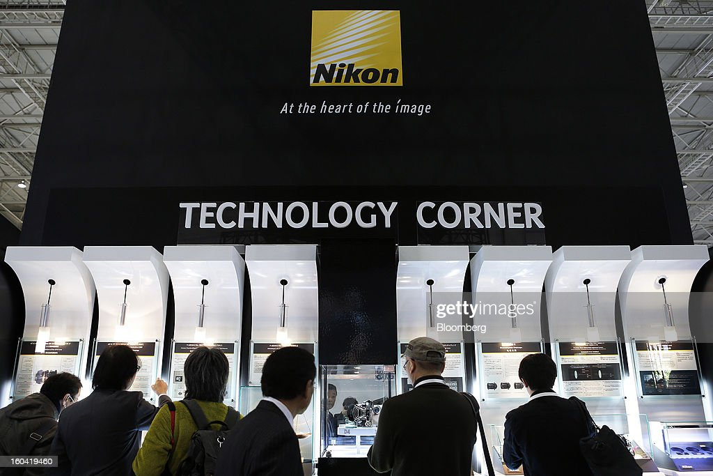 Visitors looks at a series of camera technology displays at the Nikon Corp. booth during the CP+ Camera and Photo Imaging Show in Yokohama City, Japan, on Thursday, Jan. 31, 2013. The CP+ Camera and Photo Imaging Show runs from Jan. 31 to Feb. 3. Photographer: Kiyoshi Ota/Bloomberg via Getty Images