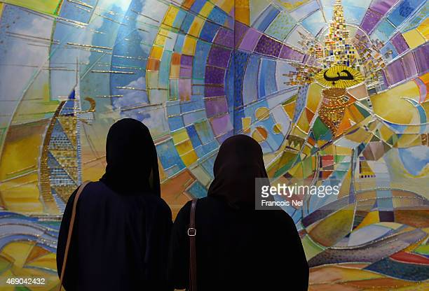 Visitors looks at artwork on display during World Art Dubai 2015 at Dubai World Trade Centre on April 9 2015 in Dubai United Arab Emirates