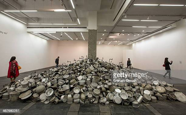 Visitors looks at Indian artist Subodh Gupta's sculpture ' This is not a Fountain ' that is part of Gupta's first major museum show in New Delhi...