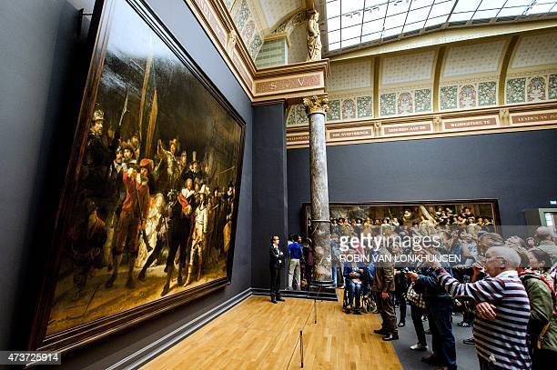 Visitors looks at Rembrandt's 'The Night Watch' in the Rijksmuseum in Amsterdam on May 17 2015 The Dutch Rijksmuseum museum was awarded the 2015...
